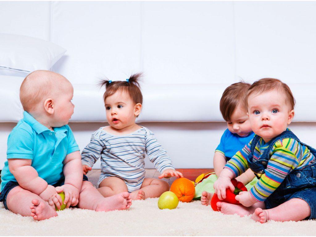Bebés jugando en la alfombra con frutas - La Tienda Home